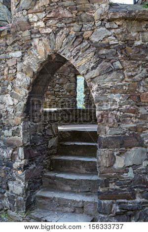 Ancient arched entrance and stone staircase leading into round watch tower. Reichenstein Castle Rhine Valley Germany - UNESCO World Heritage