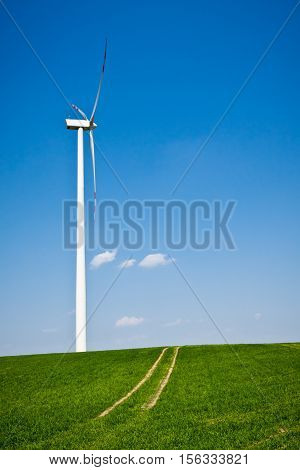 Wind Turbine With Path On Green Field With Blue Sky