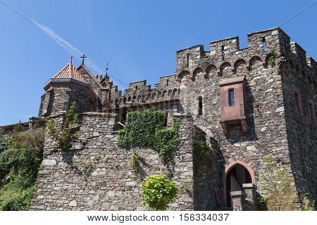 Ancient stone wall with windows stairs and carved turrets against the blue sky. Reichenstein Castle Rhine Valley Germany - UNESCO World Heritage