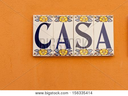 Sign CASA tiled on orange background wall