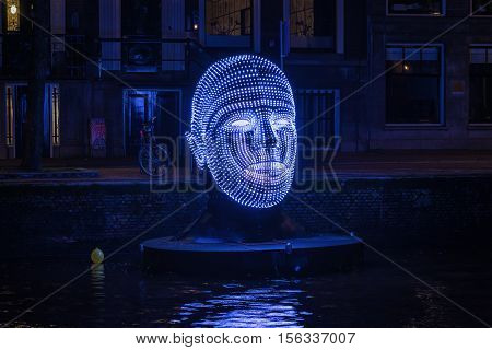 Amsterdam Netherlands - December 18 2015: Light Festival Amsterdam a floating head made of lights in an Amsterdam canal.