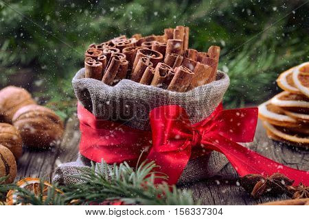 Traditional christmas spices. Stack of cinnamon in a small burlap sack. Christmas and new year decoration with anise, christmas tree and dried orange. Snow flakes.