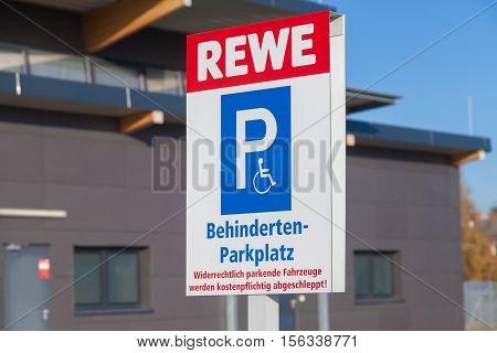 BURG / GERMANY - NOVEMBER 13 2016: handicapped parking (Behindertenparkplatz) sign on parking area from supermarket REWE.