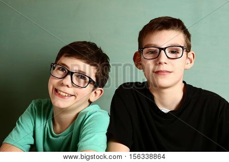 two teenager boys in myopia glasses close up portrait on blue wall background