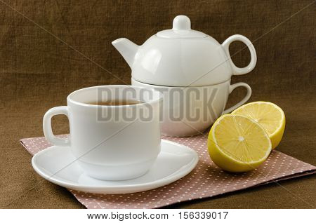 on a napkin cup of tea with lemon in a saucer and teapot, breakfast concept