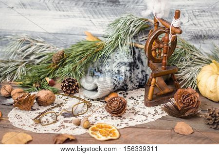 New year and Christmas winter decoration on rustic wooden background with fir branches, cones, lace, antique glasses, vintage spinning wheel, pumpkin, orange slices and walnuts. Selective focus