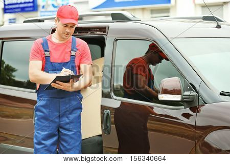 Delivery concept. Postman checking orders near a car
