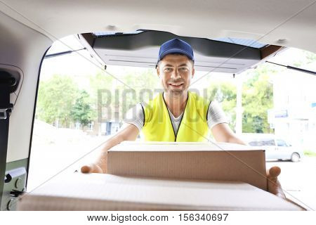 Delivery concept. Postman getting parcels from a car, view from inside