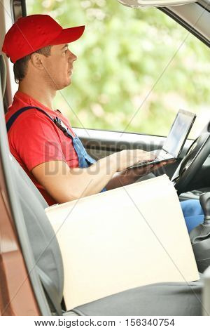 Delivery concept. Postman checking orders in a car