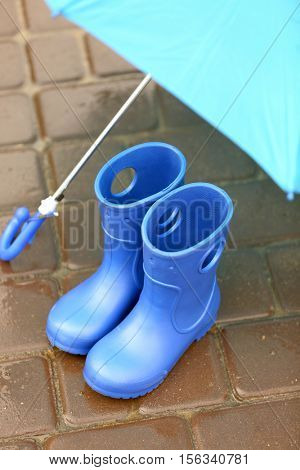 Blue umbrella and gumboots on wet pavement, close up view