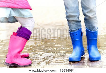 Close up view of children legs in gumboots jumping on wet pavement