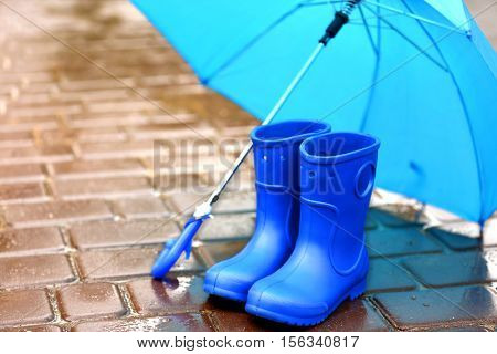 Blue umbrella and gumboots on wet pavement
