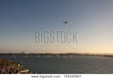 A military osprey flying over a sailboat race in San Diego Harbor California in the late afternoon.