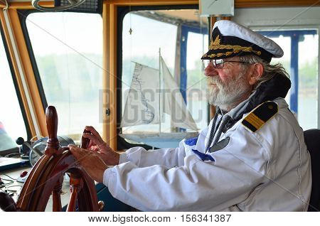 Ship navigation experienced captain old sea dog with grey hair and beard on his working place ship navigation cabine