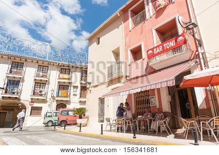 Alcalali, Spain - August 23, 2016: Spanish village scene man crosses street while women enjoy morning drink in shade outside small Spanish village bar.