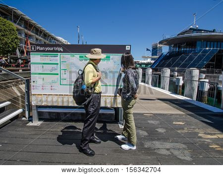 SIDNEY - AUSTRALIA NOVEMBER 2, 2016: Tourists check out the map at the promenade at Darling Harbour, one of the city's largest dining, shopping and entertainment precincts and a popular destination for visitors.