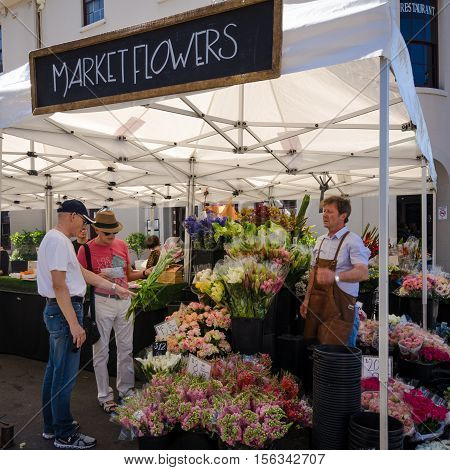 SIDNEY - AUSTRALIA, NOVEMBER 4, 2016: Couple purchases flowers from a vendor at an outdoor market.
