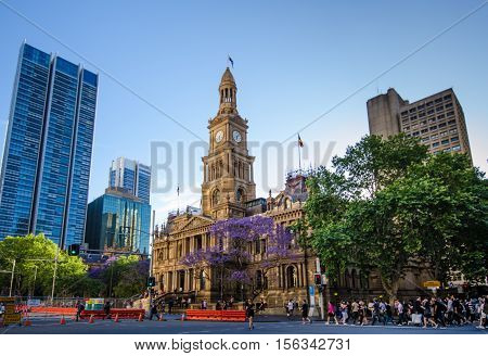SIDNEY - AUSTRALIA NOVEMBER 4, 2016: Pedestrians cross a busy street in front of the historic Victorian Town Hall on George Street in the downtown neighborhood.