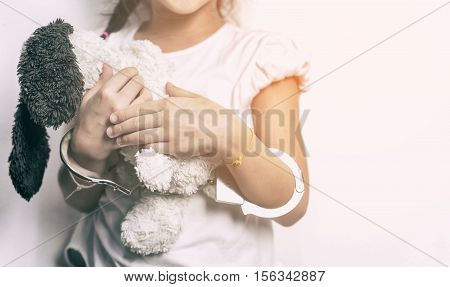 Girl is holding a doll with her hand cuffed