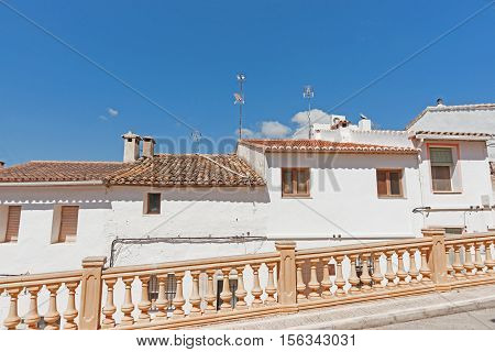 Row of terrace stile homes with Spanish terracotta roof tiles built on sloping road in Spanish village