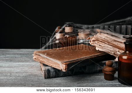 Old books with spiderweb on wooden table