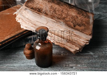 Vintage glass bottle with old books on wooden background, closeup