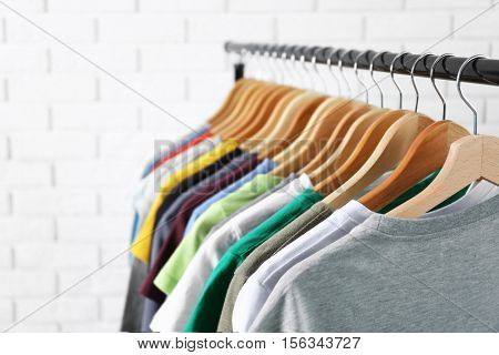 Colorful t-shirts on hangers against light blurred background, close up view