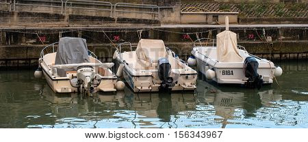 Pesaro, Italy - October 16, 2016: Motor boats at the pier on the sea. The cabins are closed covers.