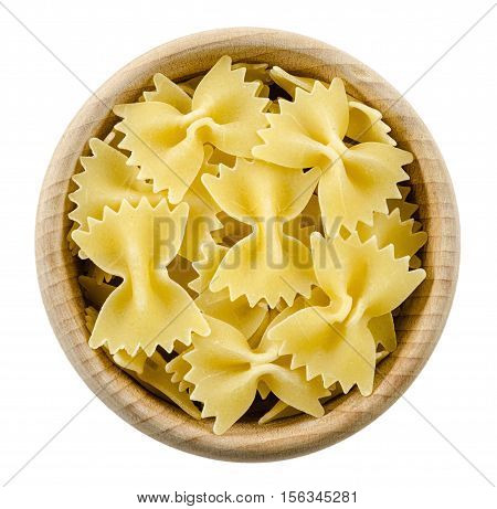 Farfalle pasta in wooden bowl. Uncooked dried durum wheat semolina pasta. Isolated on white background