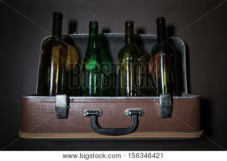 Decorative old vintage suitcase with transparent bottles inside attached to the wall