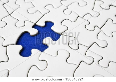 A low angle view of a white jigsaw puzzle with one missing puzzle piece.