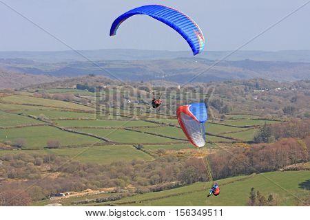 Paragliders flying their wings above Dartmoor, Devon