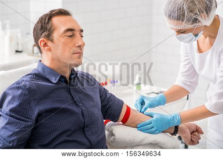 Serious man is having blood test in clinic. Nurse is sticking needle into his vein with concentration