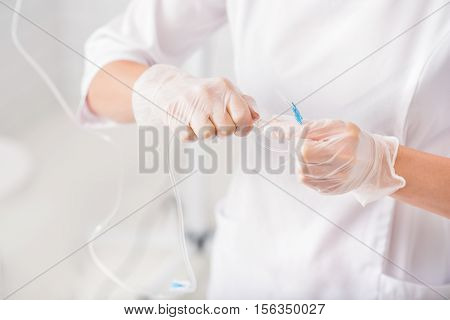 Close up of doctor hands preparing catheter for drop procedure