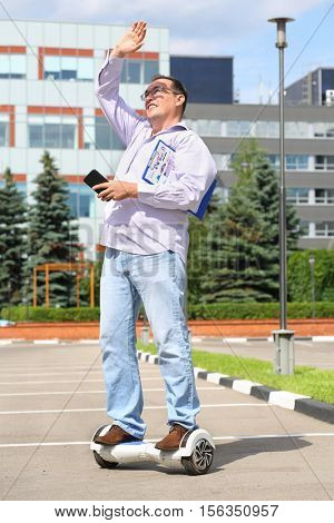 Happy man with documents, phone covers his face from sunlight on GyroScooter near building at summer