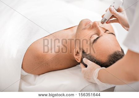 Experienced dermatologist is undergoing anti-aging ultrasound procedure at wellness center. Man is lying. His eyes are closed with pleasure poster