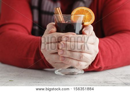 Hot Mulled Wine In Male Hands, Spices On Weathered Wooden Table. Sweet-home Concept