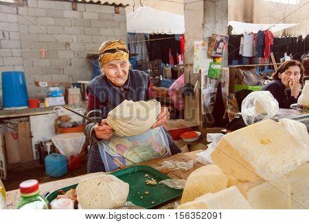 SIGNAGI, GEORGIA - OCT 7, 2016: Senior woman smiling and trading homemade cheese on Georgian rural market on October 7, 2016. Signagi of Kakhetia has a population 2.200