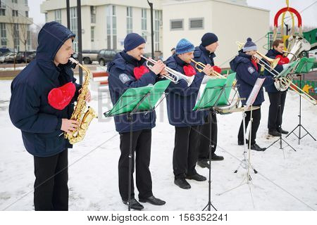 Brass band of six musicians play with notes outdoor at winter day