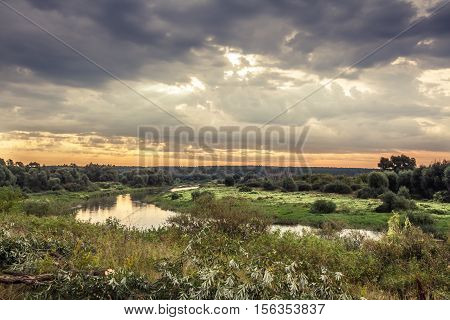 Vibrant beautiful rural landscape with dramatic sky and river during sunrise in early morning