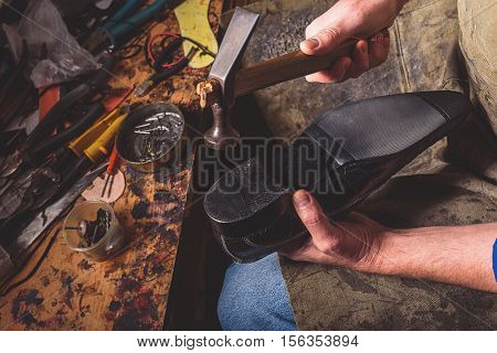 cobbler knocking at the heel of a boot with a hammer, close up