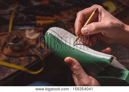shoemaker drawing details of a future footgear on a plastic pad