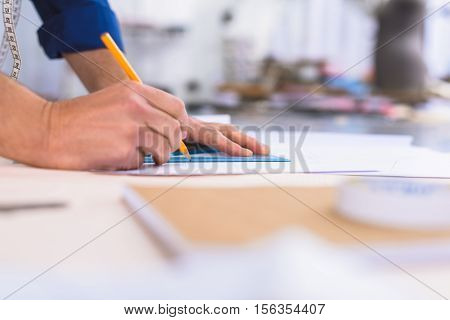 side view of a creator drawing on a table in the atelier