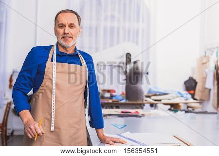 happy dressmaker in apron standing in front of his workplace, selective focus