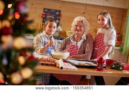 smiling kids preparing Xmas cookies with grandmother at home