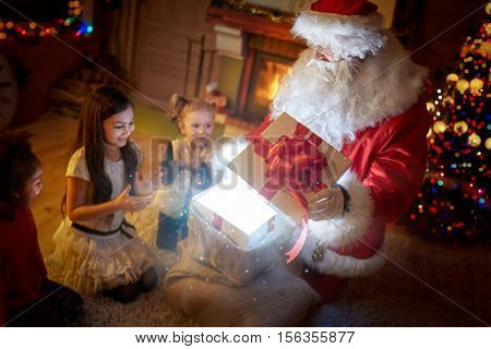 Surprised children with magical Christmas gift, Santa Claus making magic