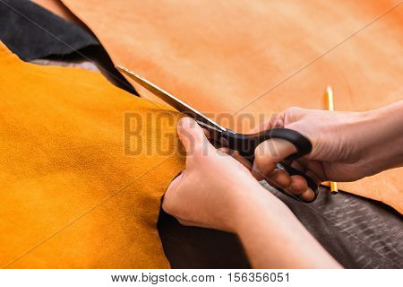 cutting of a yellow leather with tailor's scissors, close up