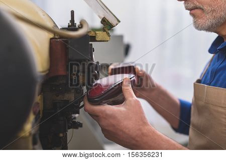 close up of a man sews a sole of a boot