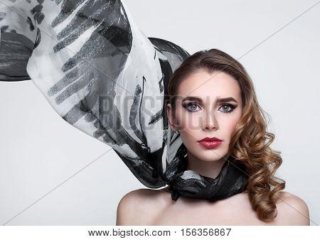 Beautiful girl with grey fashion scarf on grey background