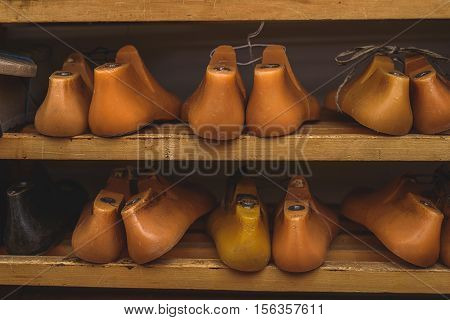 orange plastic shoe form lying on a rack, front view
